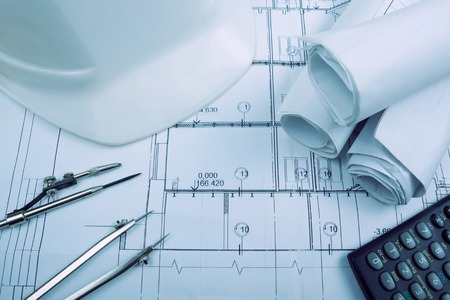 Photo pour Architectural blueprints, blueprint rolls, compass divider, calculator, white safety on graph paper. Engineering tools view from the top. Copy space. Construction background - image libre de droit