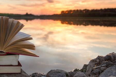 Photo pour Stack of books and Open hardback book on blurred nature landscape backdrop against sunset sky with back light. Copy space, back to school. Education background - image libre de droit