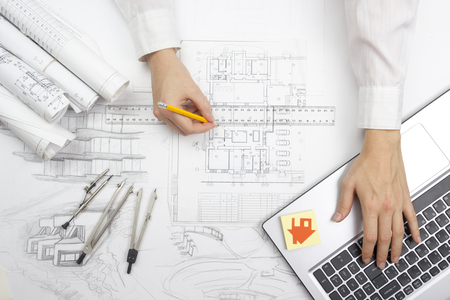Photo pour Architect working on blueprint. Architects workplace - architectural project, blueprints, ruler, calculator, laptop and divider compass. Construction concept. Engineering tools. - image libre de droit