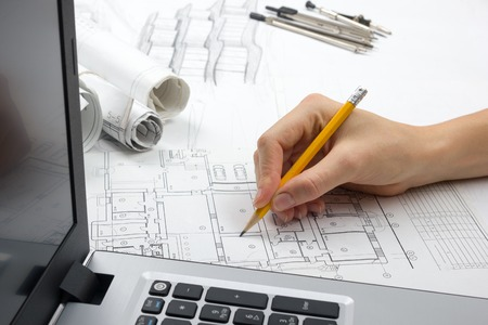 Foto de Architect working on blueprint. Architects workplace - architectural project, blueprints, ruler, calculator, laptop and divider compass. Construction concept. Engineering tools. - Imagen libre de derechos