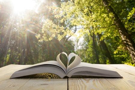 Foto de Open book on wooden table on natural blurred background. Heart book page. Back to school. Copy Space. - Imagen libre de derechos