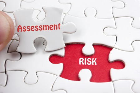 Foto de Risk Assessment. Missing jigsaw puzzle pieces with text - Imagen libre de derechos