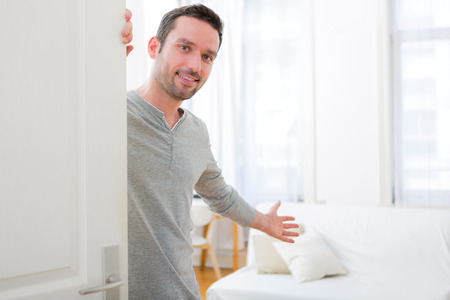 Foto de View of a Young attractive man welcoming you in his house - Imagen libre de derechos