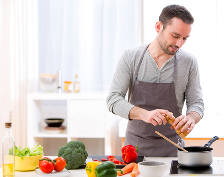 View of a Young attractive man cooking in a kitchen