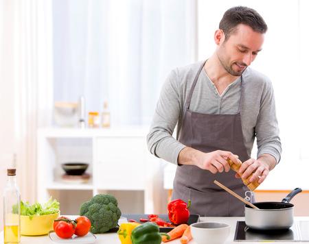 Foto de View of a Young attractive man cooking in a kitchen - Imagen libre de derechos