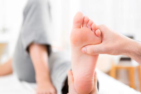 Foto de View of a Young attractive physiotherapist doing reflexology on a patient feet - Imagen libre de derechos