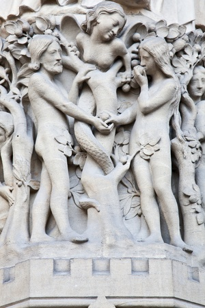 Detail on Notre Dame de Paris Cathedral fachade: Adame, Eve and the forbidden apple