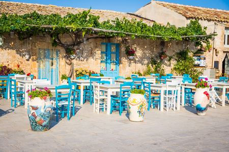 Foto de Tables and chairs setup in a traditional Italian restaurant in Marzamemi - Sicily during a sunny day - Imagen libre de derechos