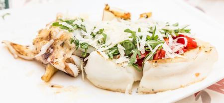 Photo pour Italian Restaurant in Gallipoli, Puglia Region (South Italy). Traditional cuttlefish with fresh salad, tomatoes and real Parmigiano cheese. Daylight. - image libre de droit