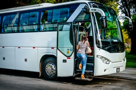 Foto per transport, tourism, road trip and people concept - passenger boarding to travel in bus - Immagine Royalty Free