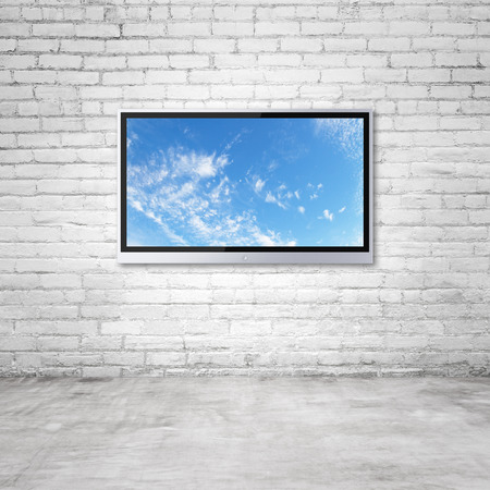 Photo for wide screen TV with sky on brick wall in room - Royalty Free Image