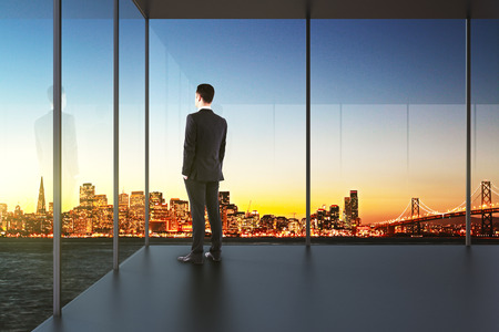 Photo for businessman in the office looking over the city at sunset - Royalty Free Image