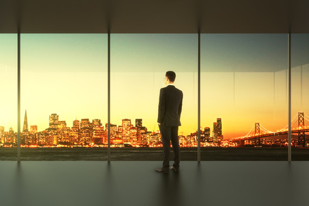 Photo pour Businessman in empty office stands at the window - image libre de droit