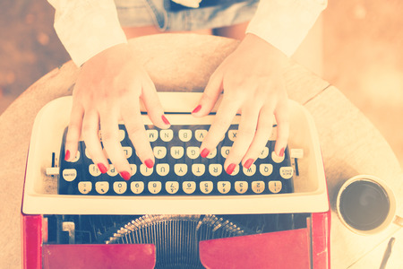 Photo pour Girl at the table typing on a typewriter, vintage photo effect - image libre de droit