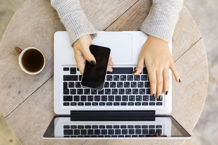 Photo pour Girl with cell phone, laptop and cup of coffee - image libre de droit