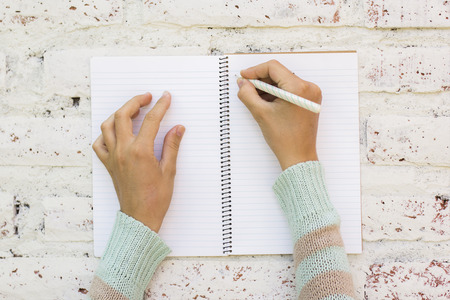 Photo pour Girl writes in notebook - image libre de droit