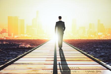 Photo pour Businessman walking on a straight road to the big city at sunrise - image libre de droit