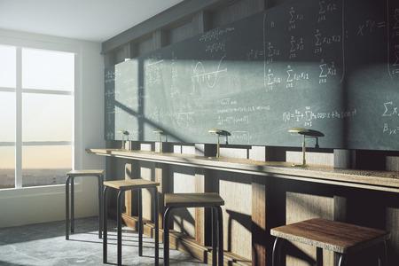 Foto de Vintage college classroom with equation solution on blackboard at sunrise - Imagen libre de derechos