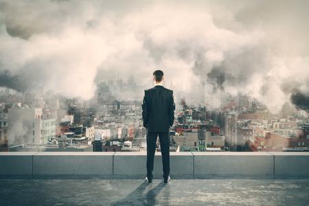 Foto de Businessman on the top of building and looking at foggy city - Imagen libre de derechos