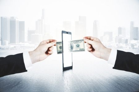 Photo for A man passes another man money through smartphone, online money transfer concept - Royalty Free Image