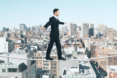 Photo pour Businessman is walking on a rope at city background - image libre de droit