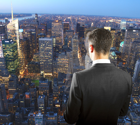 Businessman on the top of skyscraper looking at night megapolis city