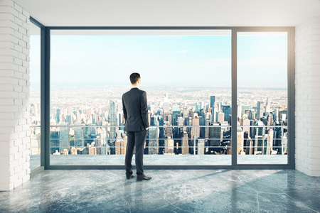 Photo for Businessman in empty loft style room with concrete floor and city view - Royalty Free Image