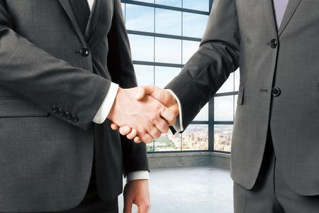 Business partners shake hands in empty loft office