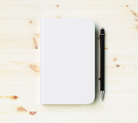 Foto de Blank white diary cover with pen on wooden table, mock up - Imagen libre de derechos