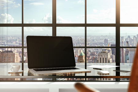 Foto de Blank laptop on a glass table in a modern office and city views from the windows - Imagen libre de derechos