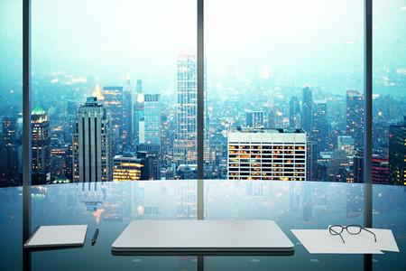 Foto de Modern office with glassy table, laptop and night megapolis city view - Imagen libre de derechos