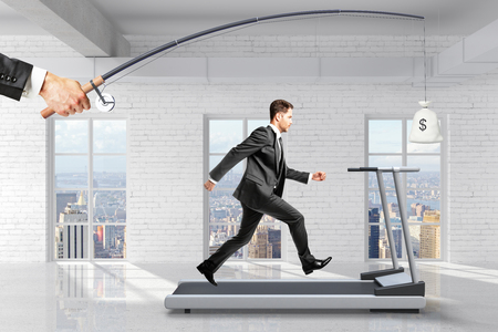 Foto de Profit-seeking concept with businessman running on a treadmill for a bag of money hanging on a fishing tackle - Imagen libre de derechos