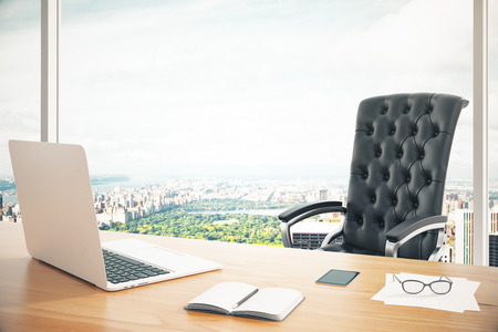 Foto de Modern work place with wooden table, laptop and classic leather chair at city background - Imagen libre de derechos