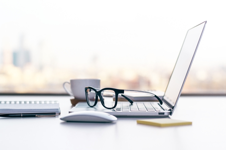 Photo pour Sideview of office desk with laptop, glasses and other items - image libre de droit