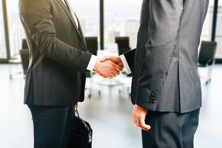Businesspeople shaking hands on office background