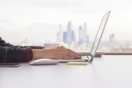 Photo for Female hands keyboarding on laptop placed on white desktop with computer mouse and smartphone with blurry city in the background - Royalty Free Image
