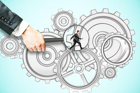 Foto de Hand holding magnifier over tiny businessman running on abstract cogwheel sketch. Blue background. Teamwork concept - Imagen libre de derechos