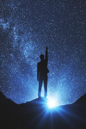 Photo pour Back view of businessman in space reaching out for the stars. Dreams concept - image libre de droit