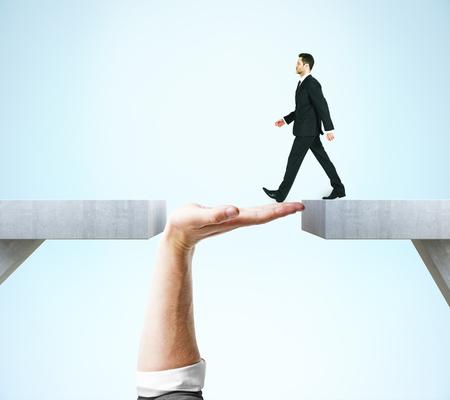 Foto de Businessman crossing abstract hand bridge on blue background. Teamwork concept - Imagen libre de derechos