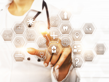 Foto de Front view of female doctor's hand pointing at abstract digital icons. Technology concept - Imagen libre de derechos
