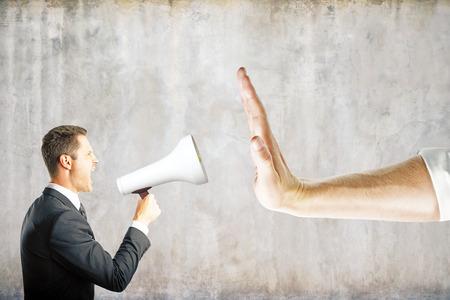 Foto de Hand gestures no to businessman screaming into megaphone on concrete background. Communication concept - Imagen libre de derechos