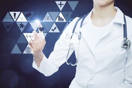 Foto de Female doctor pointing at digital medical icons on dark blue background. Digitization concept - Imagen libre de derechos
