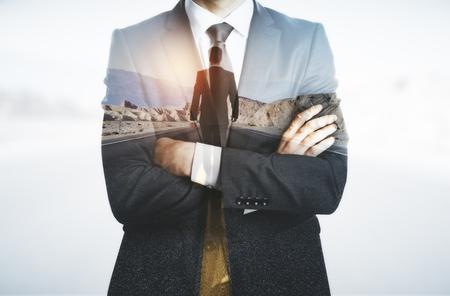 Foto de Young businessman with folded arms thinking about way to success. Future concept. Double exposure - Imagen libre de derechos