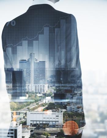 Photo pour Unrecognizable businessman on abstract city background with business chart. Finance concept. Double exposure - image libre de droit