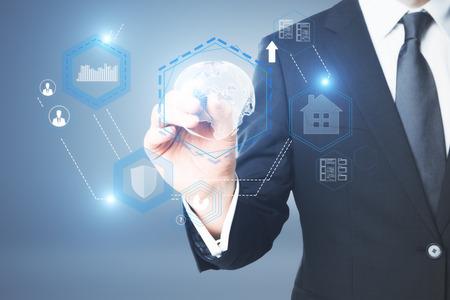 Photo pour Businessman drawing abstract digital business hologram on blue background. Antivirus concept - image libre de droit
