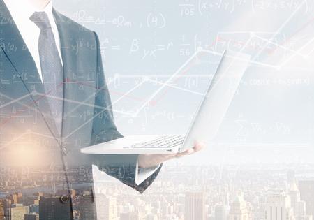 Foto de Unrecognizable businessman holding laptop on abstract city background with mathematical formulas. Technology and science concept. Double exposure  - Imagen libre de derechos