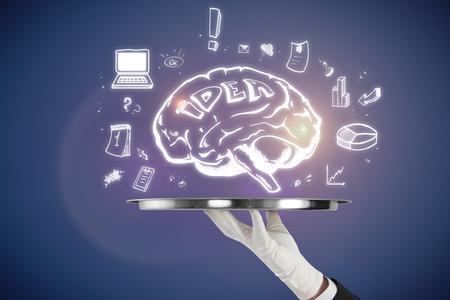 Foto de Hand holding tray with brain sketch on blue background. Brainstorming and marketing concept  - Imagen libre de derechos