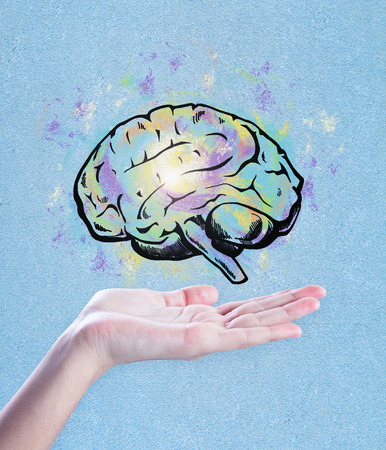 Foto de Hand holding brain sketch on blue background. Brainstorming and art concept  - Imagen libre de derechos