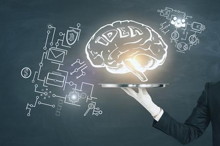 Foto de Businessman hand holding tray with glowing brain sketch on chalkboard background. Intelligence and idea concept - Imagen libre de derechos