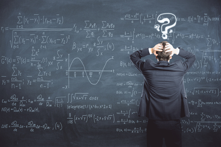Photo pour Back view of stressed businessman standing on chalkboard background with mathematical formulas. Science and trouble concept  - image libre de droit